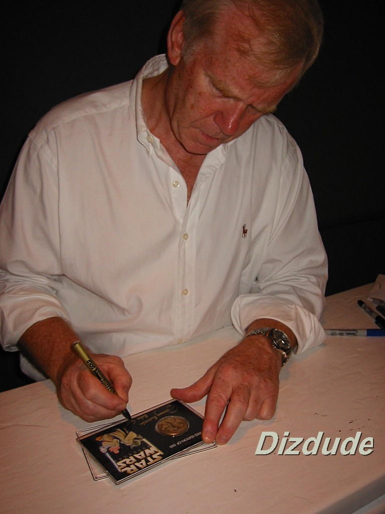 """Photo of Jeremy Bulloch (Boba Fett) signing the """"BOUNTY HUNTERS"""" Exclusive 2003 Disney Star Wars Collectors Bronze Coin With 4 Star Wars Weekends Autographs (which you will recieve with your coin) © Dizdude.com"""