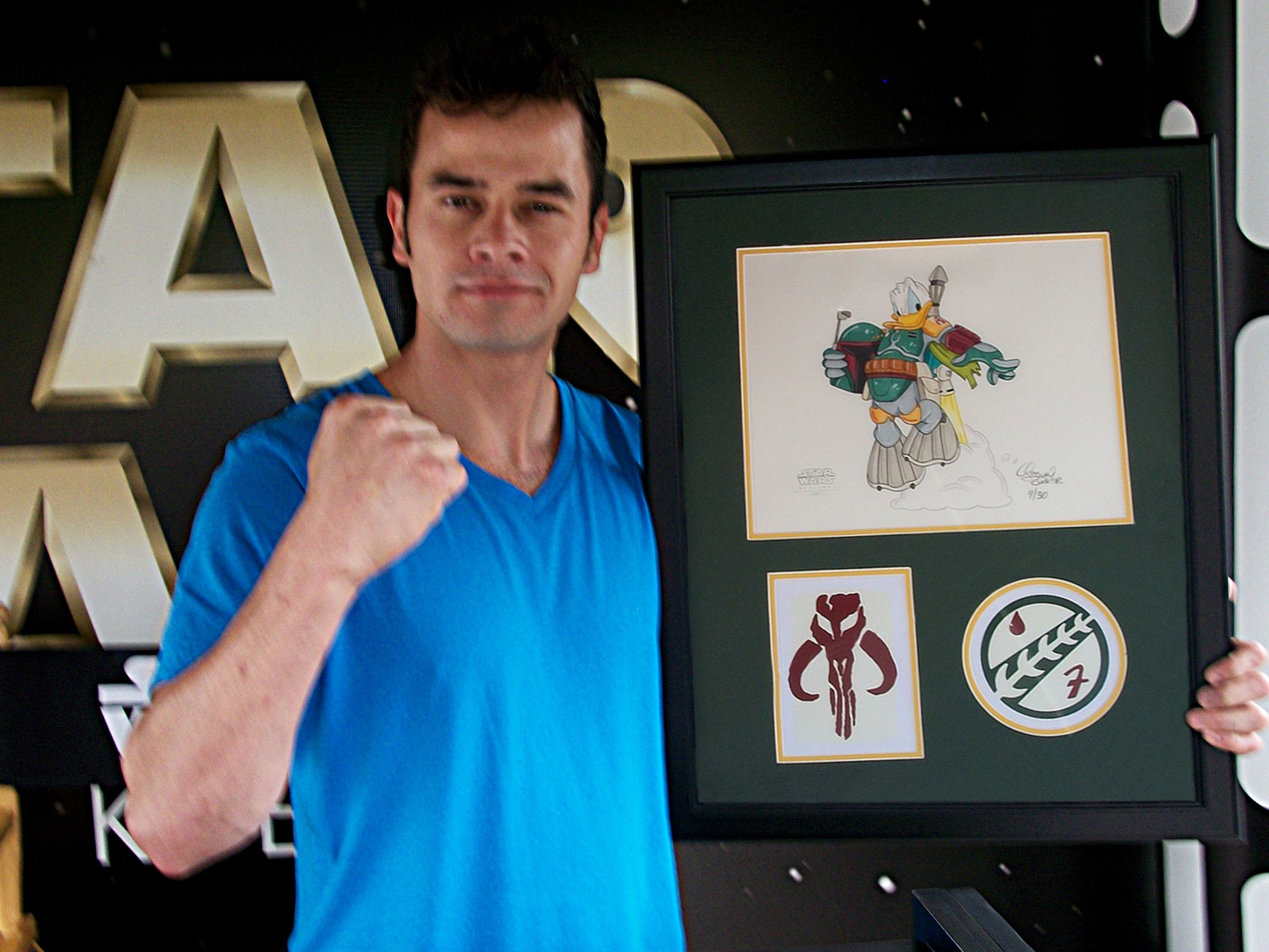 """Daniel Logan (the young Boba Fett) holding the illustration """"Donald Duck as Boba Fett"""" after signing it during Star Wars Weekends 2012  ~ © DIZDUDE.com"""