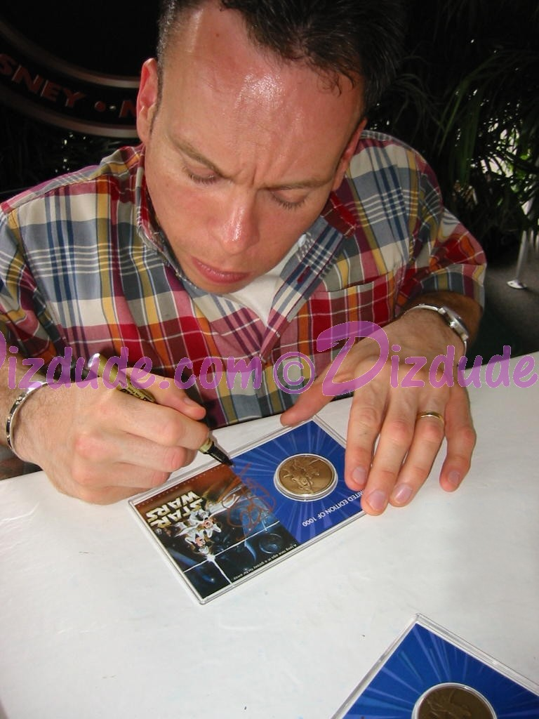 Warwick Davis (Wicket) signing and dating this Star Wars Weekends bronze Limited Edition 1000 coin 6-6-04 You will receive this photo with this coin ~ © Dizdude.com